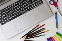 Laptoptastatur und etwas Gegenstände wie Stift, farbige Bleistifte, Filzstifte, Scheren auf weißer Tabelle Beschneidungspfad eing Lizenzfreie Stockbilder