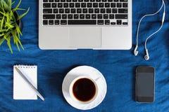 Laptoptastatur, weiße Tasse Tee auf Untertasse, Notizblock, Stift und Grünpflanze in der Ecke auf dunkelblauem zerknittertem Jean Lizenzfreies Stockbild