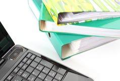 Laptopu i kartoteki falcówki na białym tle Zdjęcia Royalty Free