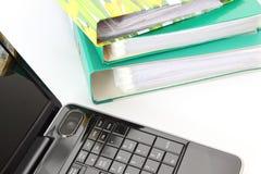 Laptopu i kartoteki falcówki na białym tle Zdjęcie Stock