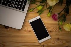 Laptopu, smartphone i eustoma kwiaty na drewnianym backgr, Obraz Stock