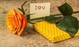 A laranja aumentou, presente coberto em papel hearted e nota eu te amo Foto de Stock