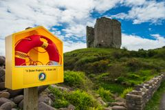 Laranja brilhante ringbuoy na frente de uma torre velha, Irlanda fotos de stock royalty free