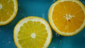 A laranja cortada que mergulha e espirra na água filme