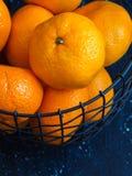 Laranja da tangerina no fundo da obscuridade da cesta de fio Imagem de Stock