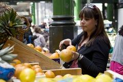 Laranja de compra da mulher nova no mercado da cidade foto de stock royalty free