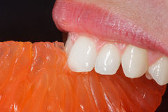 Laranja do close-up na boca do ` s da mulher foto de stock