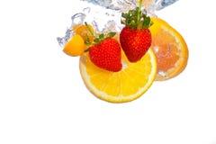 A laranja e as morangos que caem na ?gua espirram Fotos de Stock Royalty Free