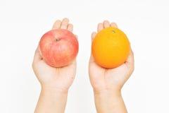 Laranja e maçã de oferecimento na mão Imagem de Stock Royalty Free