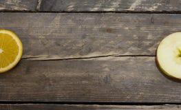 Laranja e maçã frescas em uma tabela de madeira Fotos de Stock