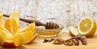 Laranja, limão e bacia pequena com mel e dipper do mel na tabela de madeira com avelã, nozes e cravos-da-índia Fotos de Stock Royalty Free