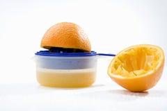 Laranja no espremedor de frutas Fotografia de Stock