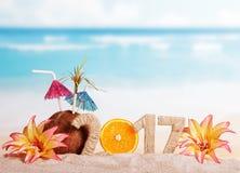 A laranja numera pelo contrário 0 em 2017, o coco, flores contra o mar Imagens de Stock