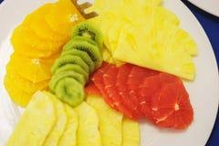 A laranja, o quivi, o abacaxi e as uvas são cortados em partes para os convidados do evento Imagem de Stock