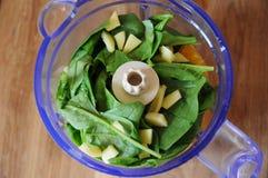 A laranja, o rabanete, os espinafres e o gengibre no misturador rolam, vista superior Imagens de Stock