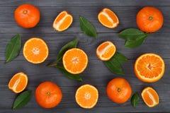 Laranja ou tangerina com as folhas no fundo de madeira preto Configuração lisa, vista superior Composição do fruto Fotografia de Stock