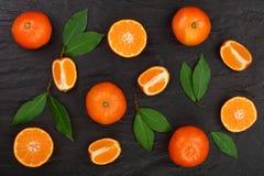 Laranja ou tangerina com as folhas no fundo de pedra preto Configuração lisa, vista superior Composição do fruto Fotos de Stock