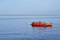 A laranja pintou a barca do metal ancorada ao longo da baía do oceano fotografia de stock royalty free