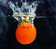 laranja suculenta saboroso brilhante alaranjada que cai na água imagens de stock royalty free