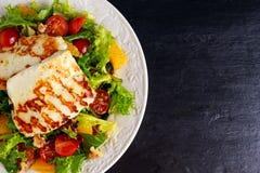 Laranja, tomates e alface grelhados da bruxa da salada do queijo de Halloumi Alimento saudável imagens de stock royalty free