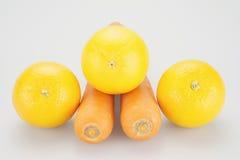 Laranjas amarelas postas sobre cenouras alaranjadas Imagens de Stock Royalty Free