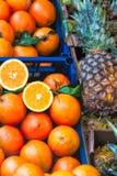Laranjas e abacaxis na exposição em um mercado local Imagem de Stock Royalty Free