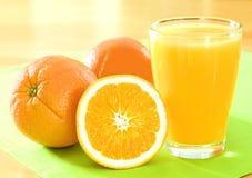Laranjas e sumo de laranja Imagem de Stock