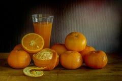 Laranjas e vidro do suco em uma tabela de madeira / Ainda fruto da vida Imagem de Stock Royalty Free