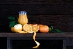 Laranjas frescas com folha e suco de laranja no vidro no tabl de madeira Imagem de Stock