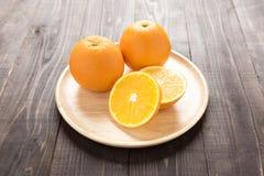 Laranjas frescas no prato de madeira, frutos frescos no fundo de madeira Fotos de Stock
