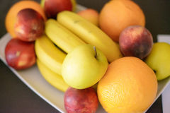Laranjas, maçãs, bananas e pêssegos em uma placa branca, com foco seletivo Fotografia de Stock Royalty Free