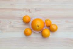Laranjas nas cestas pequenas de papel na textura de madeira com tangerinas Imagem de Stock