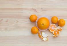 Laranjas nas cestas pequenas de papel na textura de madeira com tangerinas Foto de Stock