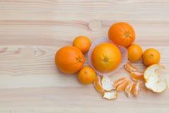 Laranjas nas cestas pequenas de papel na textura de madeira com tangerinas Fotografia de Stock Royalty Free
