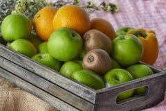 Laranjas, quivis e maçãs em uma caixa de madeira fotos de stock