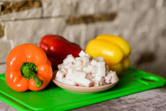 Lard cubes with bell peppers. Lard cubes in small plate with colored bell peppers on green plastic board Royalty Free Stock Image