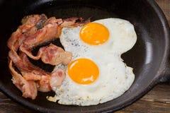 Lard et oeuf Oeuf salé et arrosé avec le poivre noir Le petit déjeuner anglais a grillé le lard, deux oeufs sur la casserole sur  Photo libre de droits