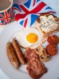 Lard et oeufs avec la tasse du thé, du pain grillé et du drapeau des anglais derrière Image stock