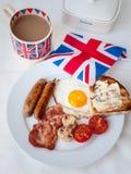Lard et oeufs avec la tasse du thé, du pain grillé et du drapeau des anglais derrière Photos stock