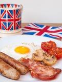 Lard et oeufs avec la tasse du thé et du drapeau des anglais derrière Photos libres de droits