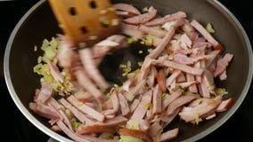 Lard et oignons frits dans une poêle Ils sont mélangés à une spatule Fin vers le haut clips vidéos