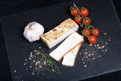 Lard with garlic and tomatoes. Close up of seasoned lard on black stone plate stock photo