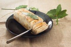 Lard with laurel leaf on a plate. Lard with laurel leaf on a black plate Royalty Free Stock Images