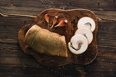 Lard roll with salt and garlic. Wooden background Stock Image