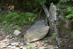 Larg rocks at creekside. Large flat stones laying on the bank of a small stream in the forest royalty free stock photography