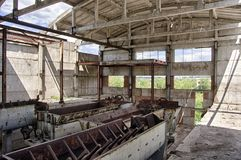Large abandoned industrial building interior. Ruined sugar refinery with rusty remnant of equipment.  royalty free stock images