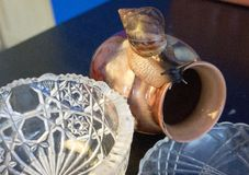 A giant snail on a clay pot looks at a crystal vase stock photography