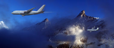 Large aircraft and small plane. On a background of high mountains Royalty Free Stock Images