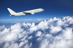 Large airliner along clouds. Large airliner climbing along cloud top against a deep blue sky Royalty Free Stock Photo