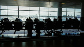A large airport terminal on a sunny day. Silhouettes of people waiting for a flight, the aircraft through the window stock video footage